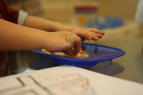 child using fingers and pincer grasp to pick up Cheerio dust