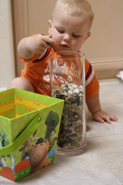 baby placing small rocks in a large glass vase