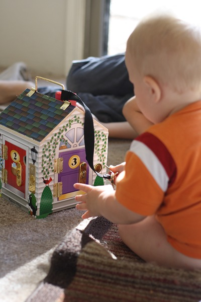 baby playing with dollhouse toy