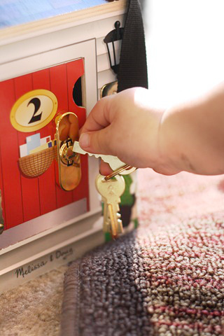 baby putting toy keys in a toy lock