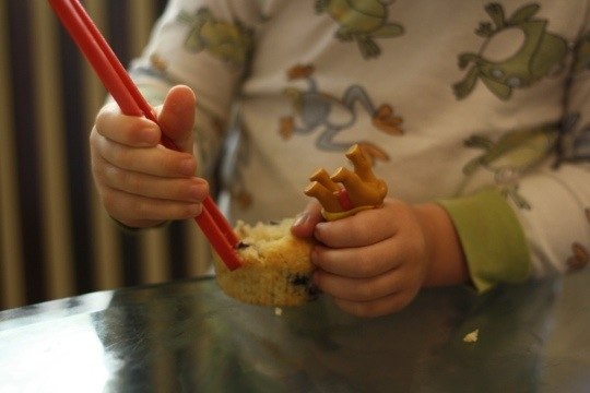 child holding beginners chopsticks