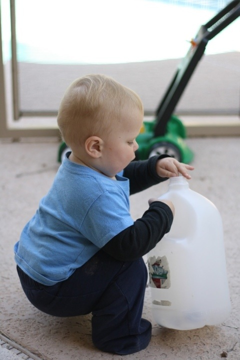 baby putting small rocks into a large water jug