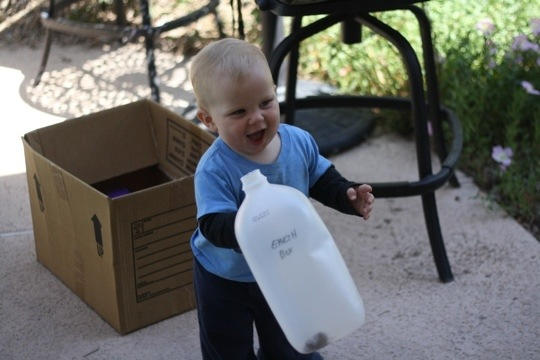 baby shaking water jug with rocks inside happily