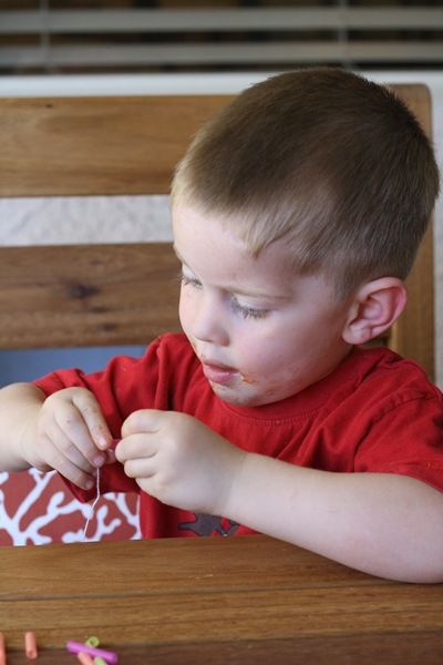 child stringing beads on a string