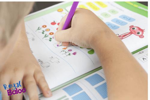 child writing on math in workbook