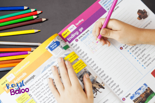 child filling out spelling words in workbook